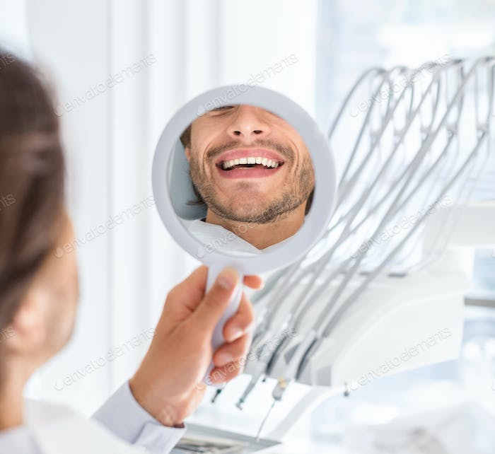 Hadsome man checking smile at mirror after treatment in clinic