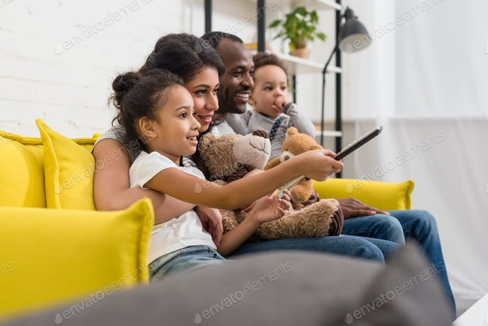beautiful young family watching tv together on couch