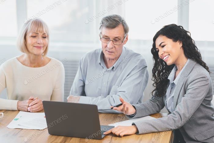 Elderly couple consulting with financial advisor at home