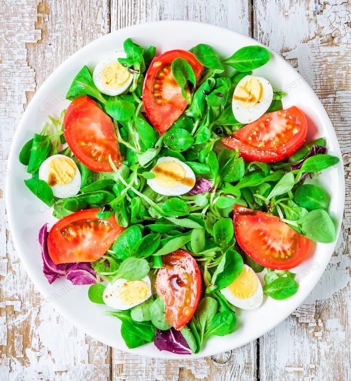 frischer grüner Salat mit Lammsalat, Tomaten und Wachteleier
