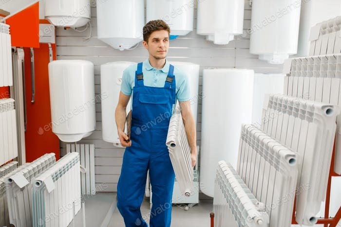 Plumber holds heating radiator, plumbering store