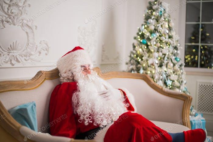 Weihnachtsmann entspannt auf Sofa gegen Weihnachtsbaum zu Hause