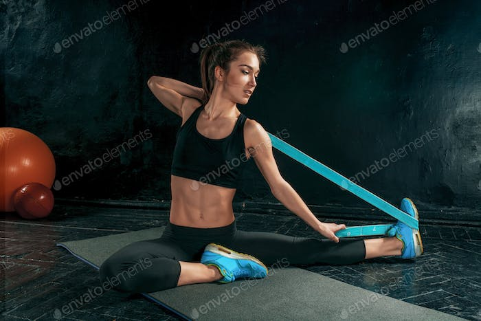 The brunette athletic woman exercising with rubber tape