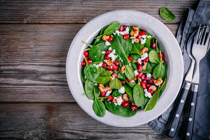 Fresh green salad with spinach, walnuts, feta cheese and pomegranate