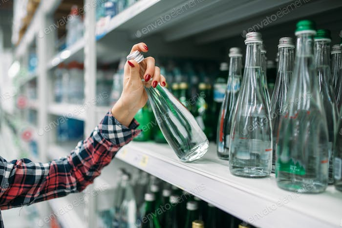Young woman buying mineral water in supermarket