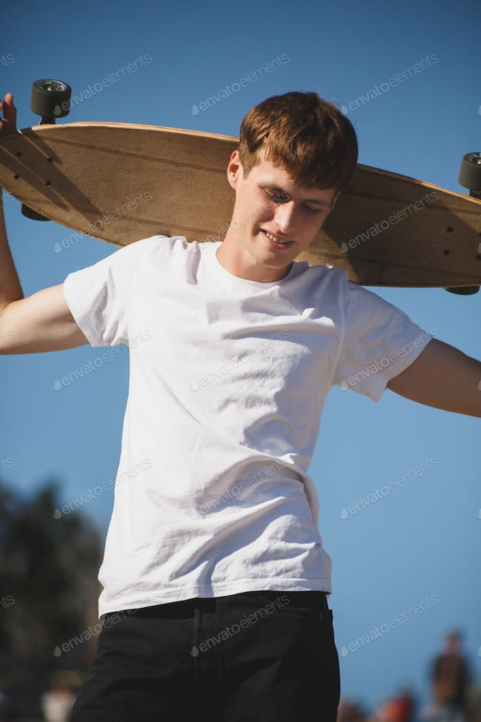 Young smiling man in white t-shirt standing with skateboard in hand