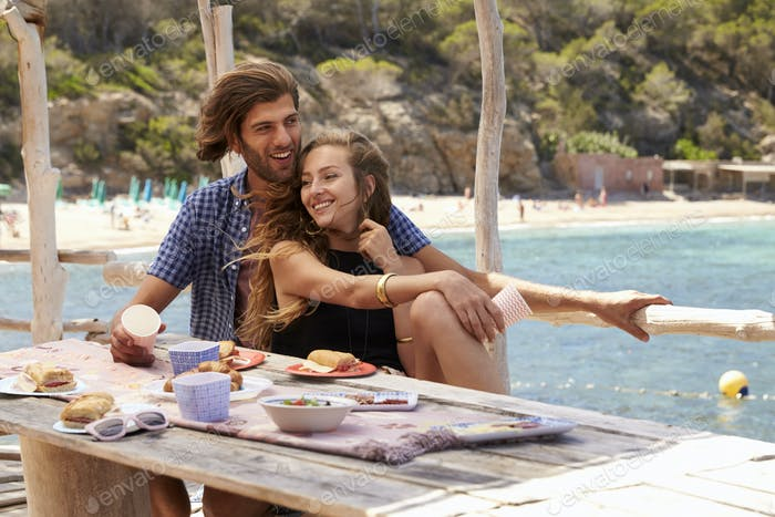 Young couple eating at a table by the sea laughing together