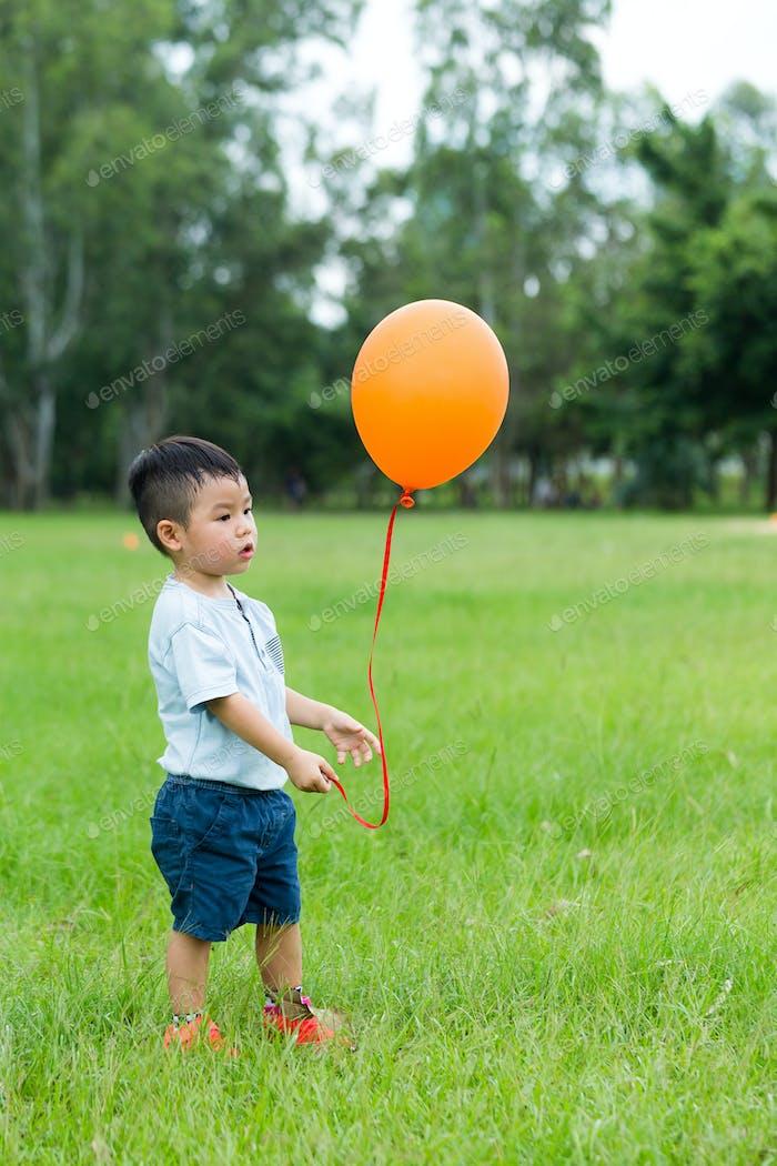 Little boy holding with orange balloon