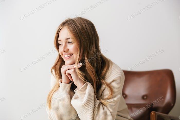 Bild der erfreuten jungen Frau lächelnd, während sie auf dem Sessel sitzen