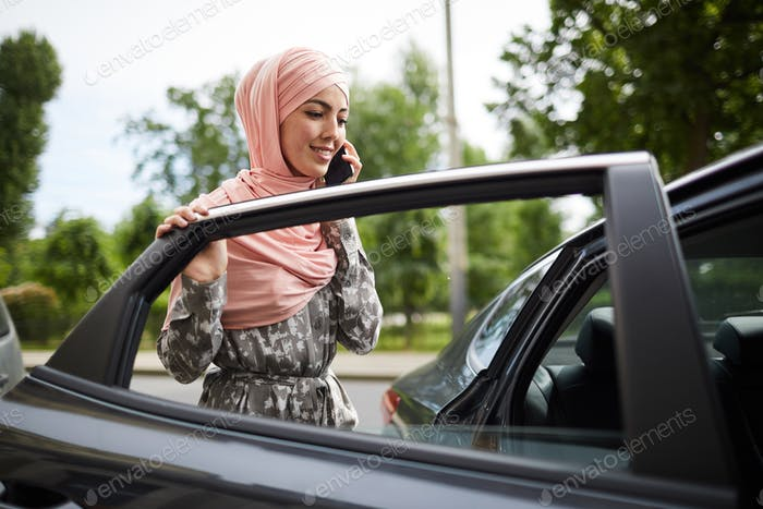 Muslim woman getting into car
