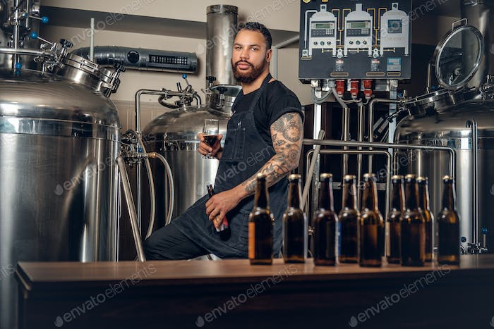 Black bearded  maler presenting craft beer in the microbrewery.