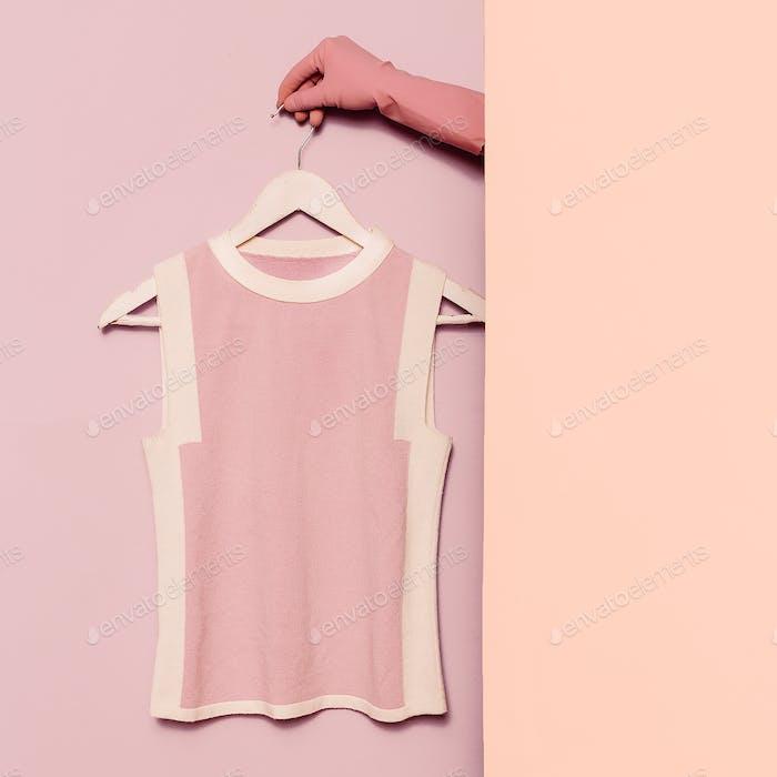 Stilvolle Kleidung. Minimale Mode. Rosa oben auf einem Kleiderbügel. Garderobe