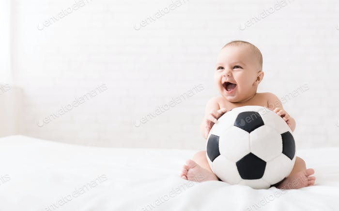 Newborn baby sitting with soccer ball on bed