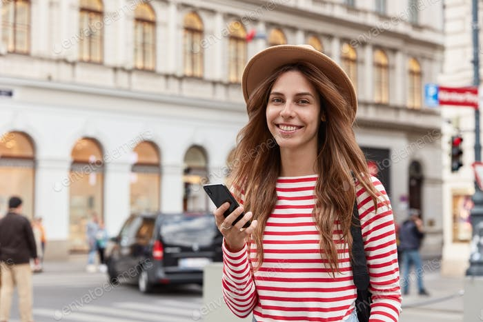 Photo of positive female uses cell phone for navigating in town, checks notification, wears hat and