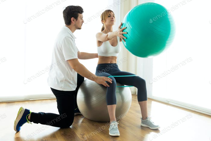 Physiotherapist helping patient to do exercise on fitness ball in physio room.