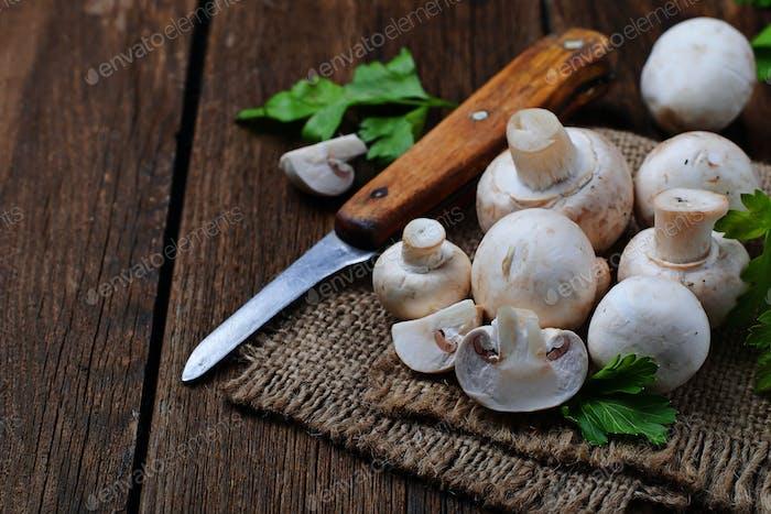 Raw champignon mushroom on wooden background