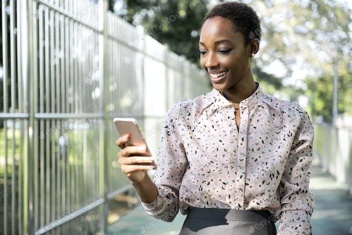 negro señora mensajes de texto en su teléfono mientras caminar en un parque