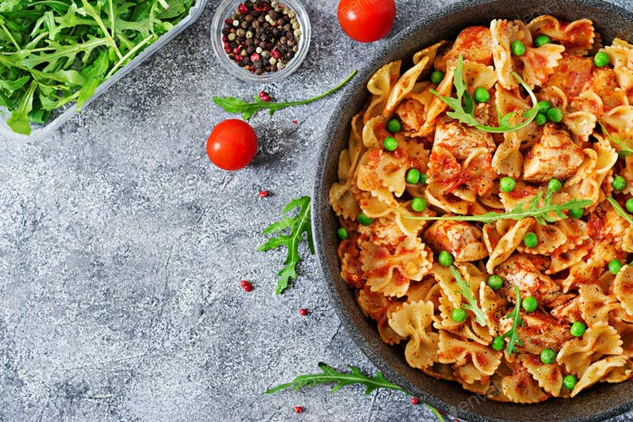 Farfalle pasta with chicken fillet, tomato sauce and green peas.