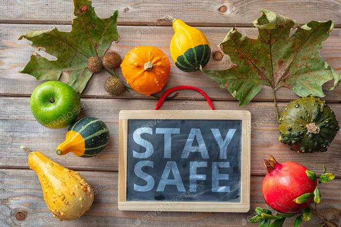 Stay safe message and thanksgiving pumpkins against wooden background. COVID 19 days