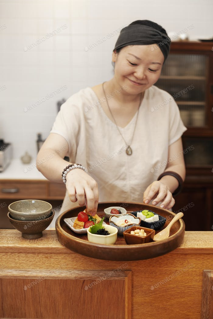 Japanese woman preparing fresh vegetables in a vegetarian cafe.