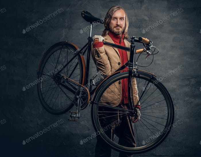 A man holds bicycle on his shoulder.