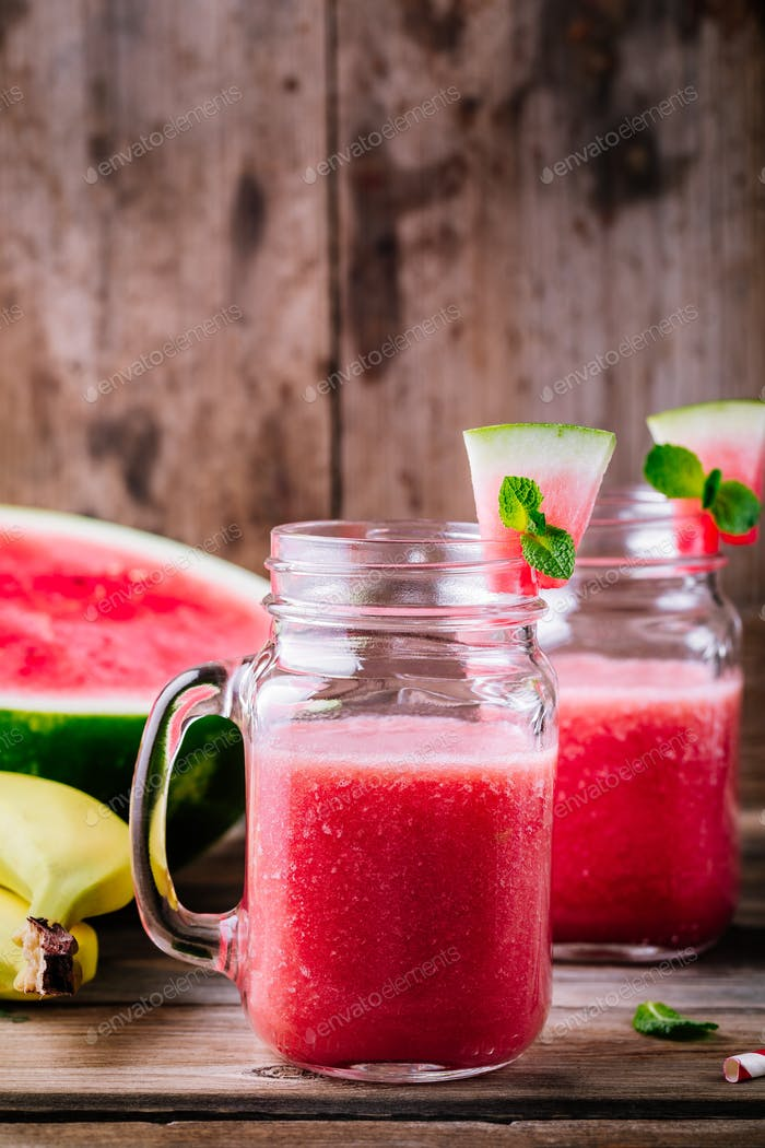 Watermelon and banana smoothie in mason jars with mint on wooden background