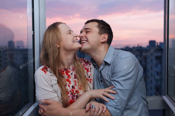 Young couple on the balcony embracing and laughing