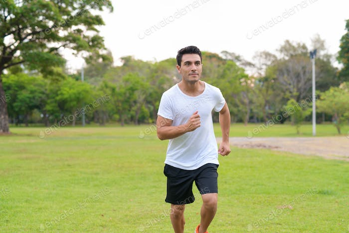 Young handsome Hispanic man jogging at the park