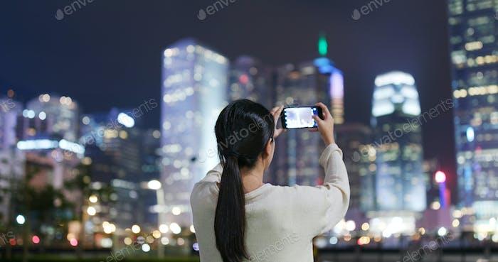 Frau fotografieren mit Handy in Hong Kong
