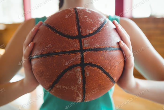 Midsection of female basketball player holding ball