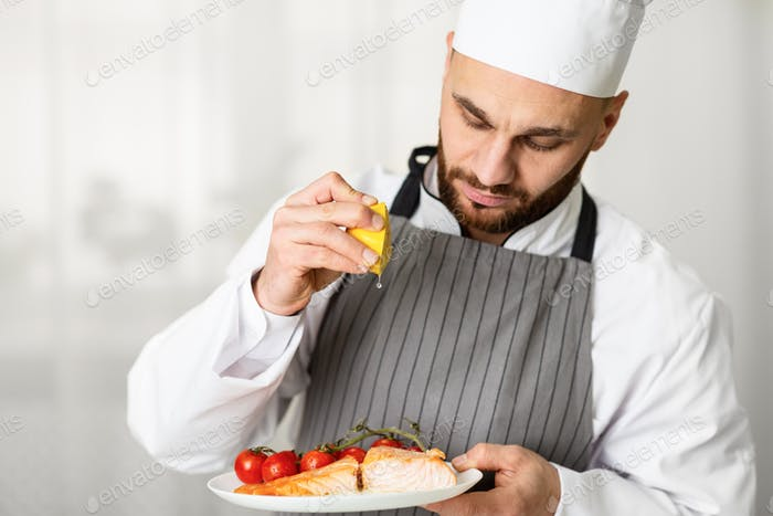Male Chef Squeezing Lemon Plating Roasted Salmon Steak In Kitchen