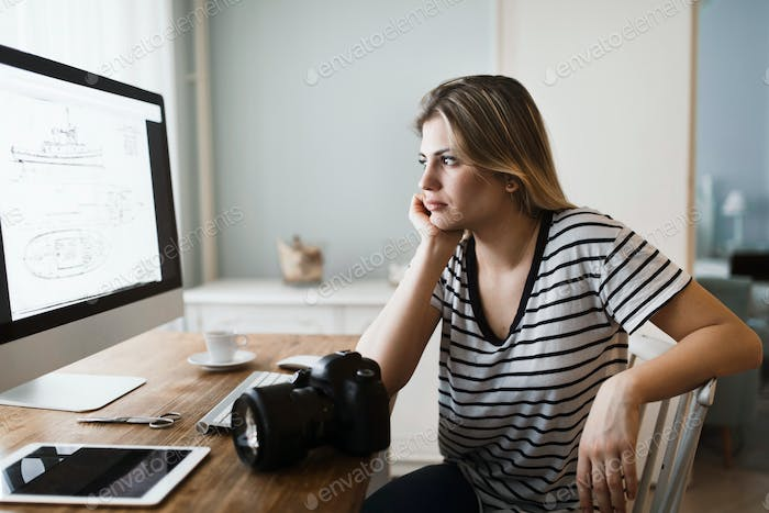 Picture of young female designer working at home