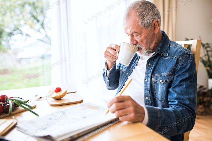 Senior man eating breakfast at home.