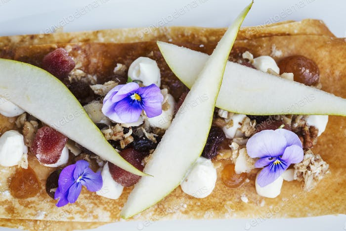 A dessert dish on white plate with layers of mille feuille pastry and pear slices and fresh flowers.