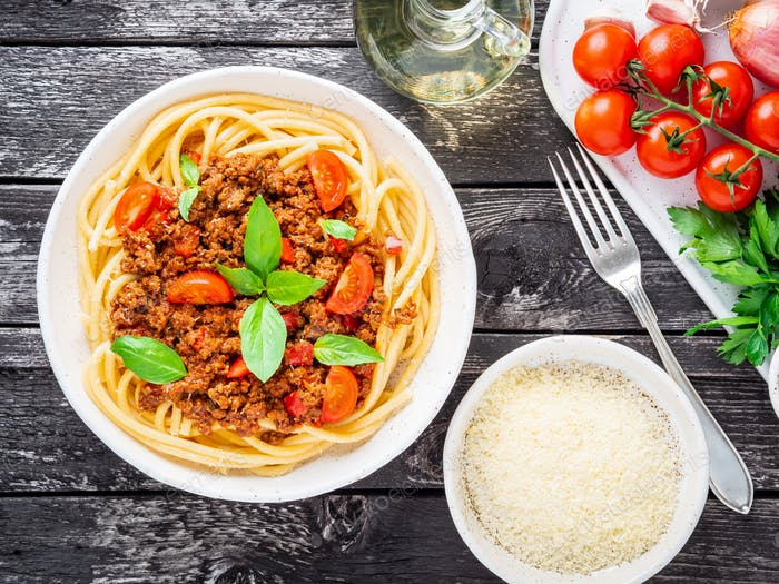 pasta bolognese with tomato sauce, ground minced beef, basil leaves on background