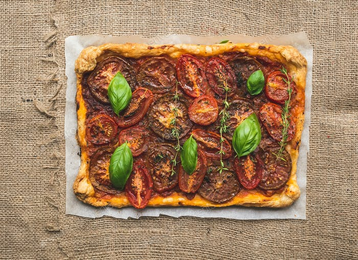 Rustic tomato autumn pie on a silver tray over a sackcloth surfa