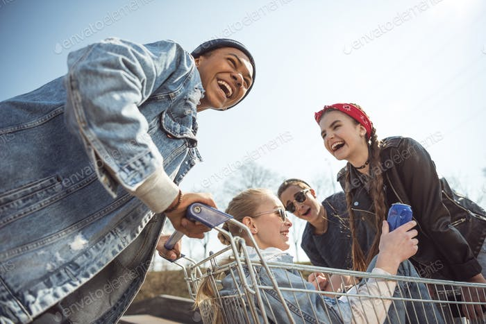 Smiling Teenagers Group Having Fun With Shopping Cart at Skateboard Park