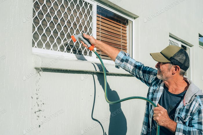 Man cleans window with flow of water by hose pipe