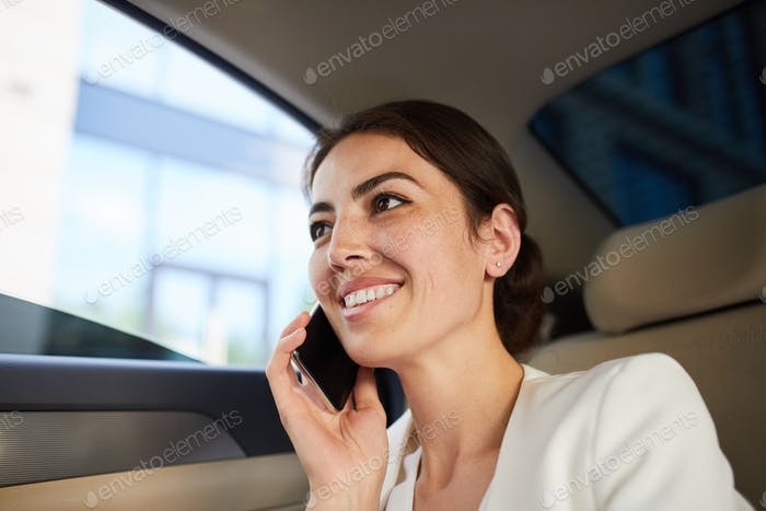 Woman Speaking by Smartphone in Car