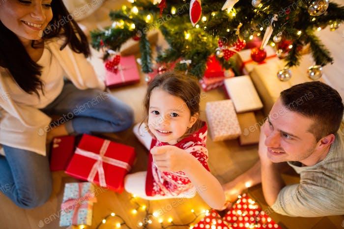 Junge Familie mit Tochter am Weihnachtsbaum zu Hause.