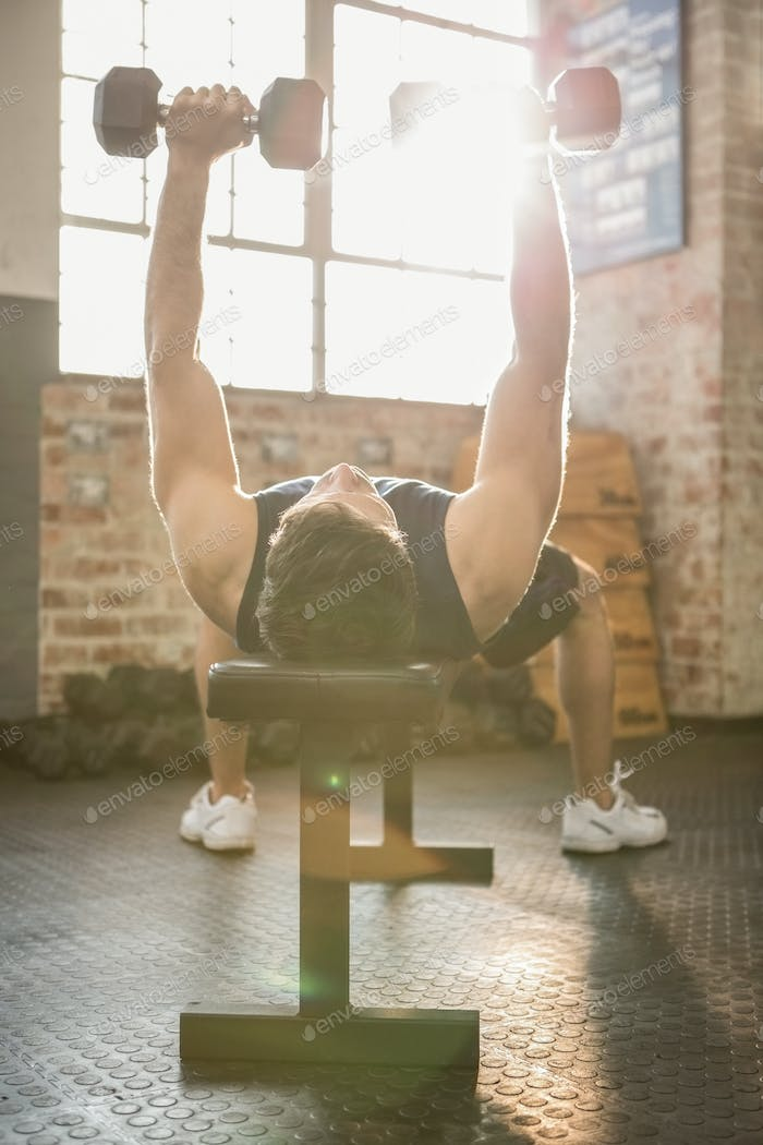 Muscular man lifting dumbbells lying on bench at the gym