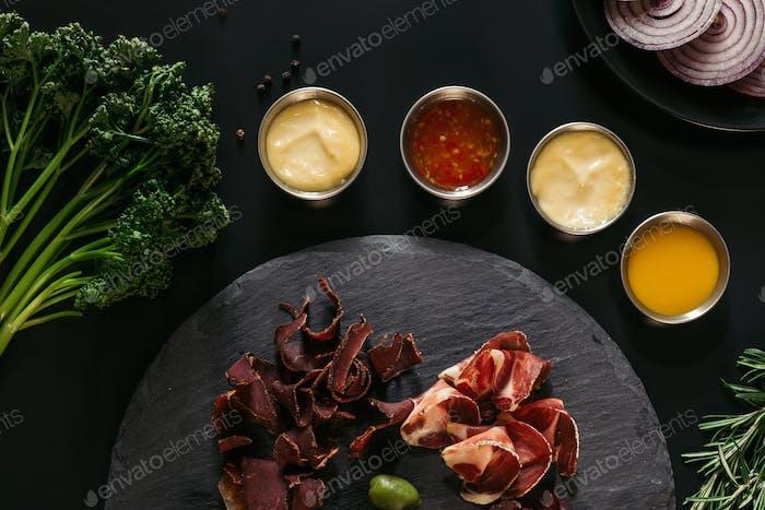 Draufsicht auf Gourmet-Bastelfleisch mit verschiedenen Saucen auf Schwarz
