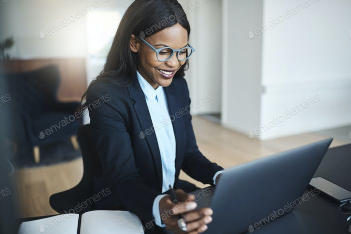 Young African American businesswoman smiling while working at her desk