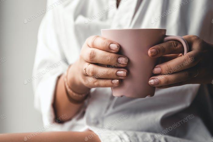 Frau in einem weißen T-Shirt hält Morgenkaffee in einer rosa Keramiktasse. Maniküre. Vorderansicht