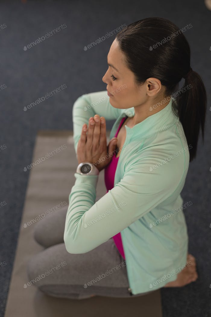 High angle view of young beautiful woman doing yoga in fitness studio
