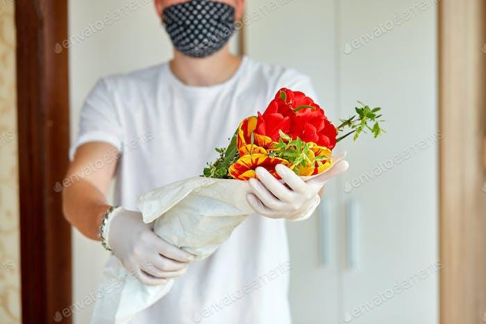 Kurier, Lieferung Mann in medizinischen Latex-Handschuhe sicher liefert Online-Käufe einen Blumenstrauß