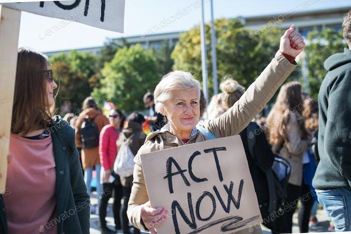 Senior con cartel y cartel sobre la huelga mundial por el cambio climático