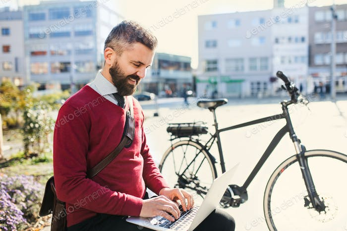 Hipster businessman commuter with bicycle on the way to work in city, using laptop.