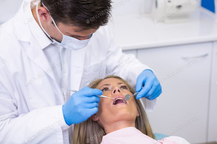 Dentist examining woman at dental clinic