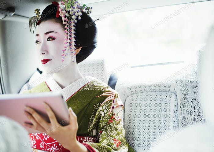 Женщина, одетая в традиционный гейшский стиль, носит кимоно со сложной прической и